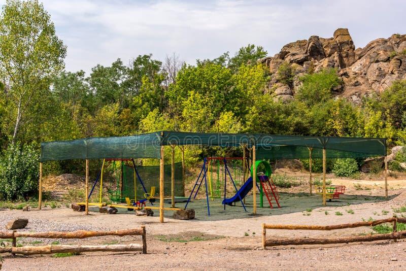 儿童的体育操场在一个机盖下露天在夏天 免版税库存图片