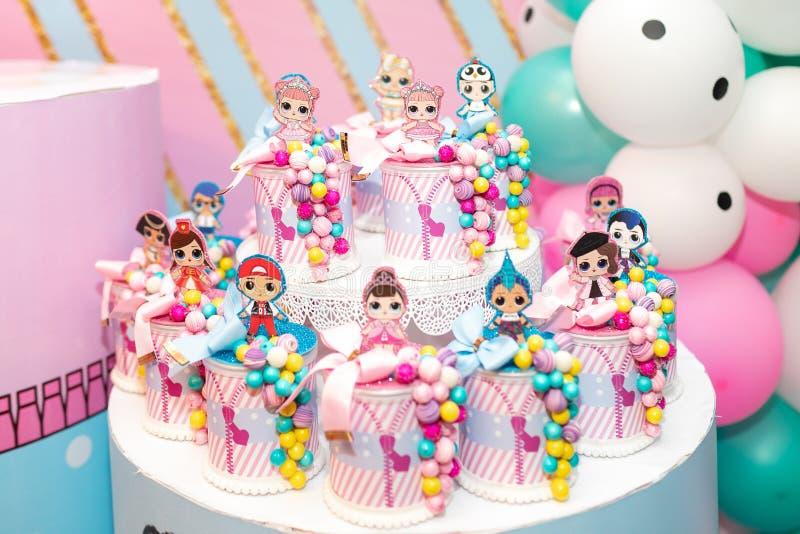 儿童的党的,在一张白色桌上的玩偶lol装饰玩具,在气球背景  库存图片