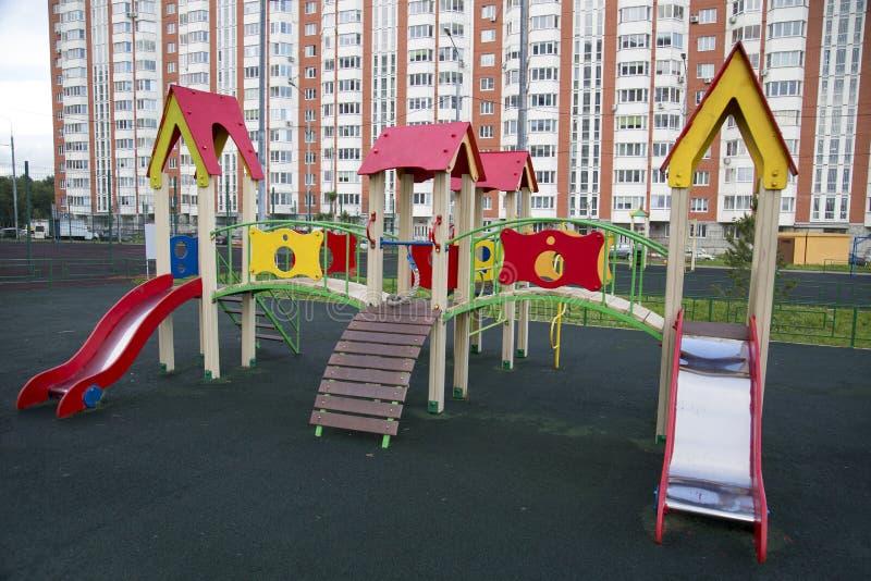 儿童的套在城市的操场的木幻灯片 库存图片