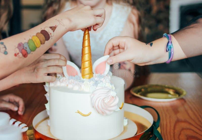 儿童的手女孩为蛋糕到达 大美好的蛋糕独角兽在生日在欢乐桌上的一点公主 库存图片