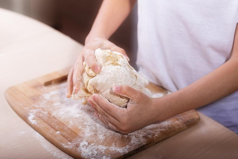 儿童的手揉在一个木切板的面团 特写镜头 面团食谱,烹调技术 库存照片