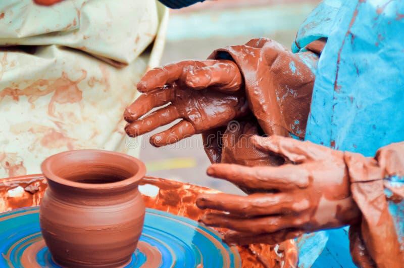 儿童的手特写镜头在雕刻在一个横式转盘的棕色黏土的一个罐有蓝色背景 免版税库存图片