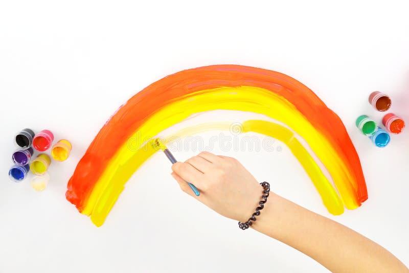 儿童的手画在白色背景的一条彩虹 库存照片