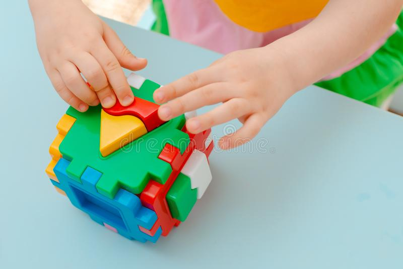 儿童的手的特写镜头收集难题整理者 与被插入的几何形状和色的塑料块的立方体 免版税库存图片