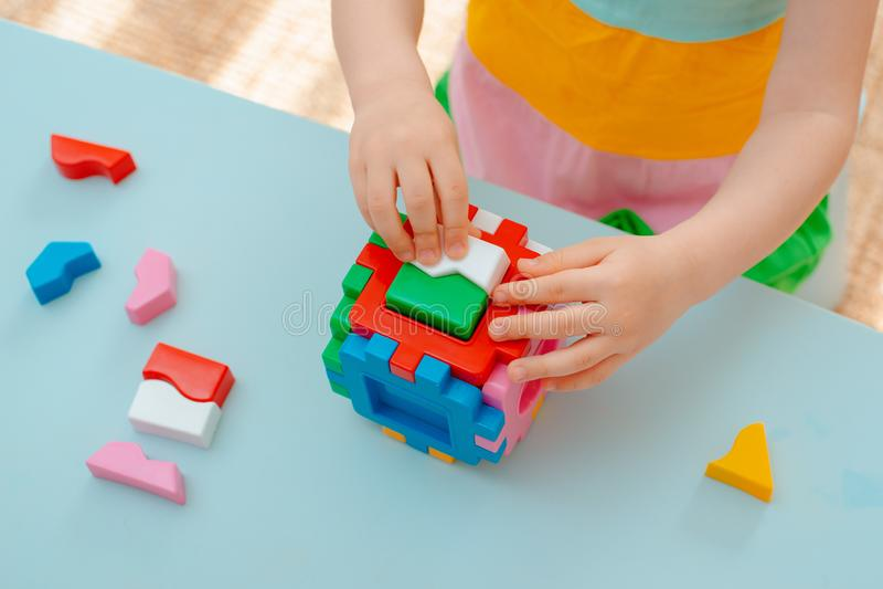 儿童的手的特写镜头收集难题整理者 与被插入的几何形状和色的塑料块的立方体 库存照片