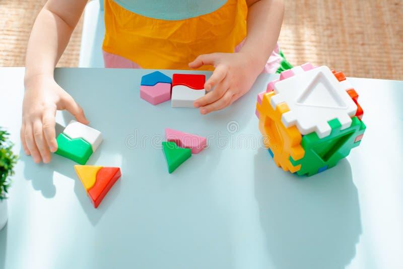 儿童的手的特写镜头收集难题整理者 与被插入的几何形状和色的塑料块的立方体 库存图片