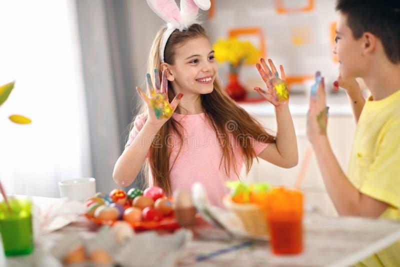 儿童的手肮脏从鸡蛋的油漆 库存照片