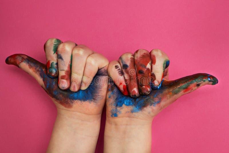 儿童的手,抹上与在桃红色背景的多彩多姿的油漆 手指向上在坚固性边 库存图片