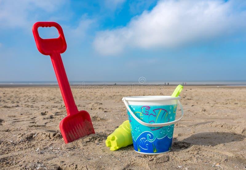 儿童的桶和小铲在海滩 免版税库存图片