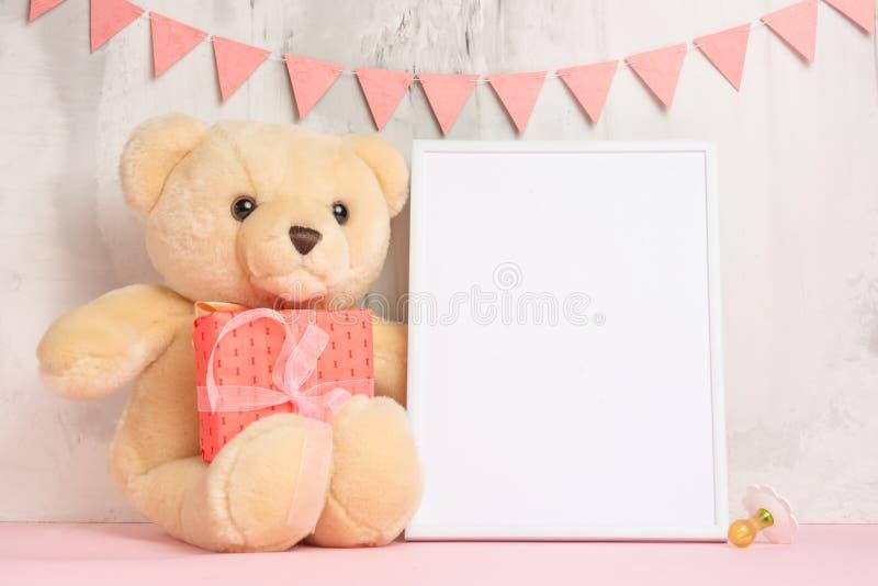 儿童的玩具、一个玩具熊和一个框架在轻的墙壁背景,设计的,布局 婴孩出生的男孩看板卡新的阵雨 免版税库存图片