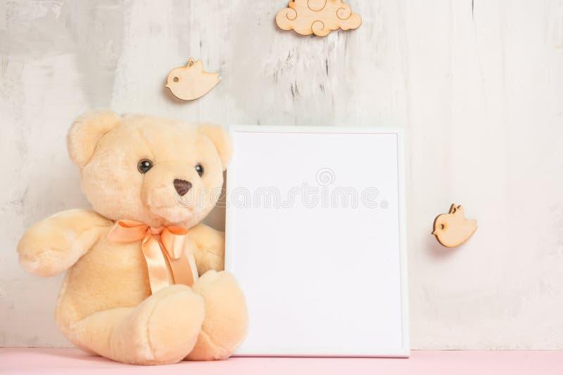 儿童的玩具、一个玩具熊和一个框架在轻的墙壁背景,设计的,布局 婴孩出生的男孩看板卡新的阵雨 库存照片