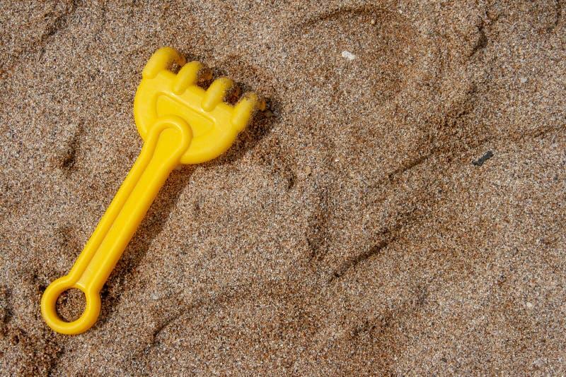 儿童的玩具犁耙和踪影他们在沙子 图库摄影
