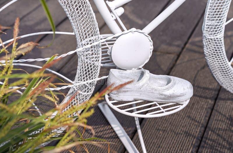 儿童的金属凉鞋在概念自行车的脚蹬 以儿童的金属凉鞋的形式庭院装饰 库存照片