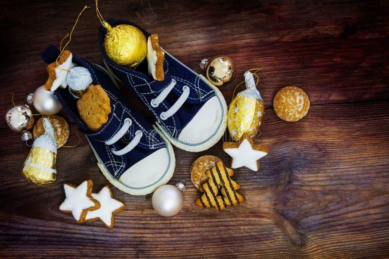 儿童的鞋子用曲奇饼和圣诞节装饰填装了为 免版税库存照片