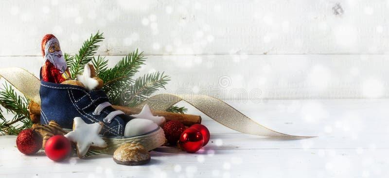 儿童的鞋子用甜点、曲奇饼和圣诞节decorat填装了 库存图片