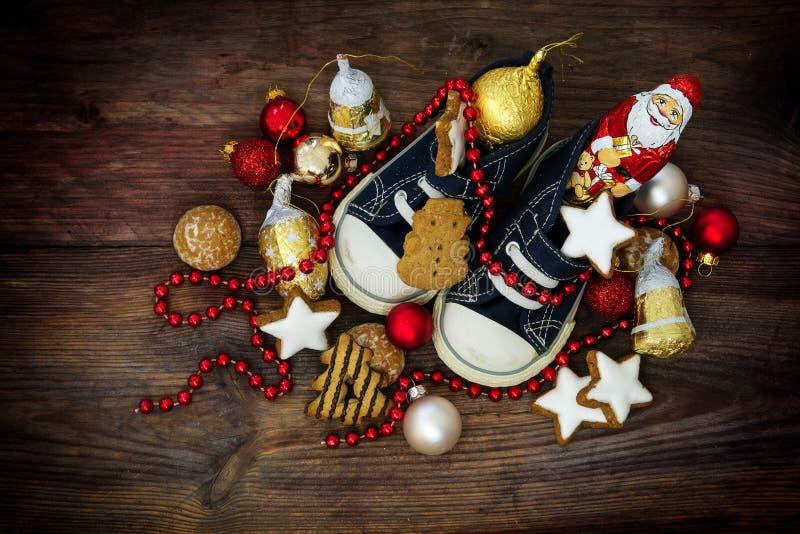 儿童的鞋子用甜点和红色圣诞节装饰填装了 免版税库存照片
