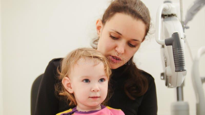 儿童眼科学-母亲和逗人喜爱的小女孩-验光师检查儿童` s眼睛 免版税库存照片