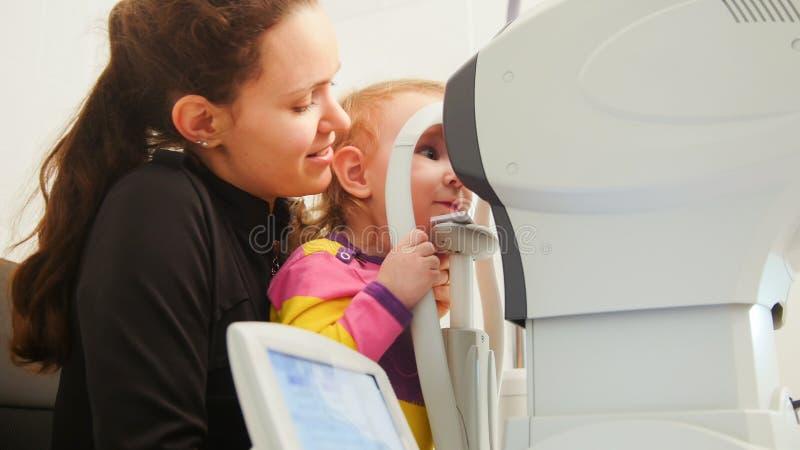 儿童眼科学-母亲和逗人喜爱的小女孩-验光师检查儿童` s眼睛 免版税图库摄影