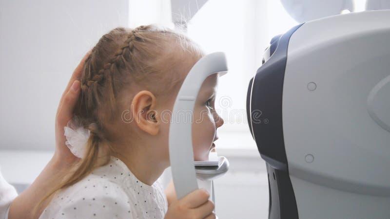 儿童眼科学-验光师检查儿童` s眼睛 库存图片