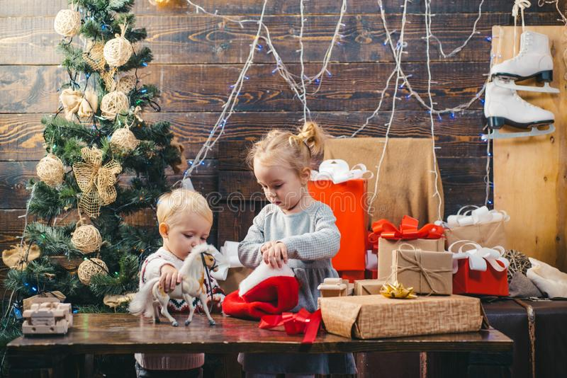 儿童礼物 在家平衡的冬天 看装饰玩具球的愉快的孩子画象由圣诞树 ? 免版税库存图片