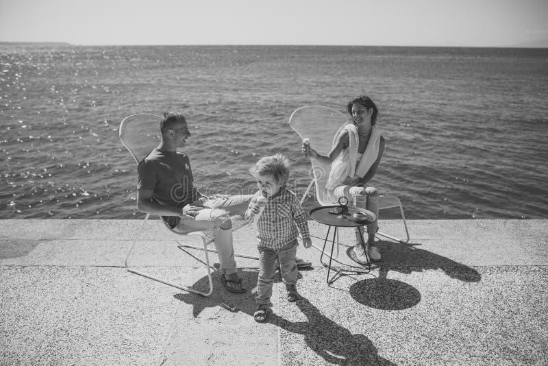 儿童童年儿童幸福概念 逗人喜爱的儿子享受暑假 有孩子的父母吃冰淇凌在 免版税图库摄影
