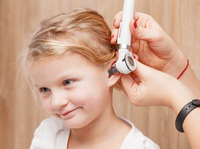 儿童耳鼻喉科的检查-医生审查的耳朵有oto的一女孩 免版税库存照片