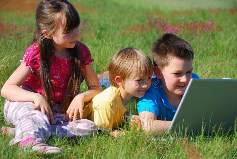 儿童膝上型计算机共享 免版税库存图片