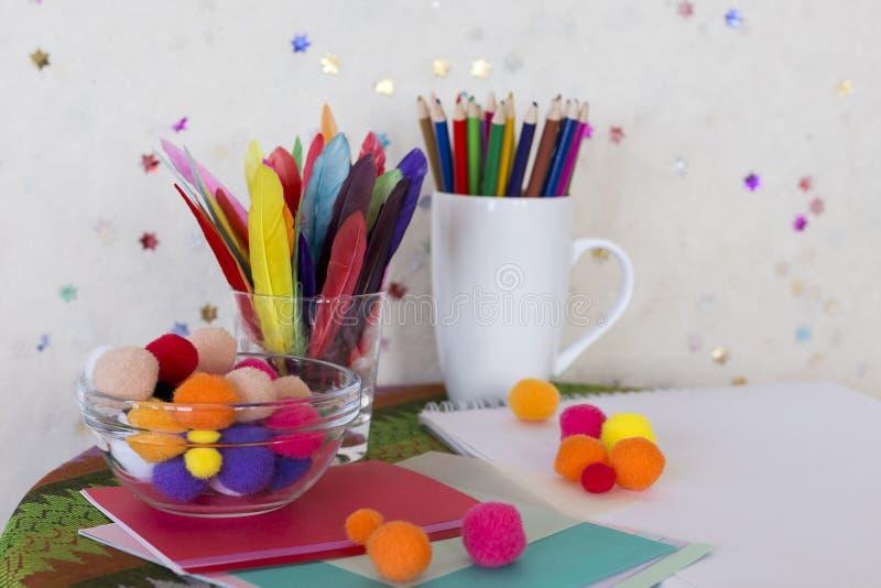 儿童艺术和工艺工作站与色的铅笔、五颜六色的羽毛、pom poms和纸 免版税图库摄影