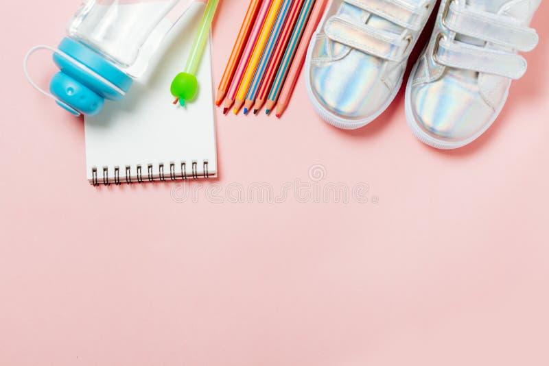 儿童衣裳和研究材料:运动鞋、铅笔、瓶水和电子gps手表 免版税库存图片