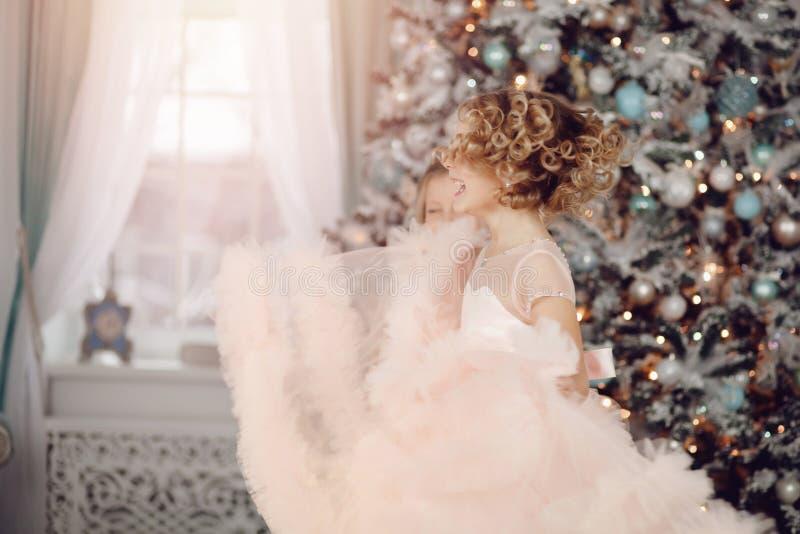 儿童转动在圣诞树背景的幸福女孩在礼服的 免版税库存照片