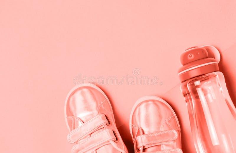 儿童运动鞋和瓶在时髦生存珊瑚背景的水 库存照片