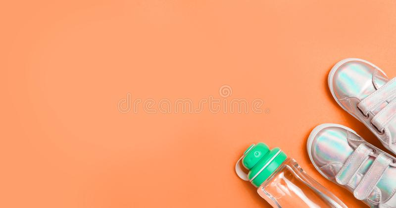 儿童运动鞋和瓶在橙色背景的水 库存照片