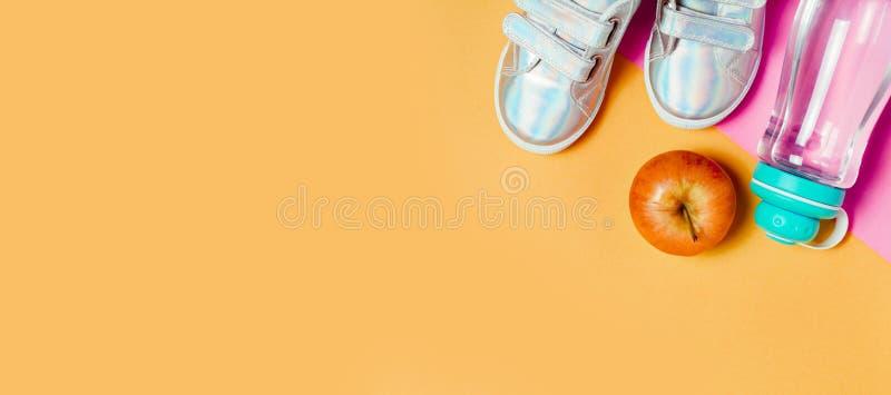 儿童运动鞋和瓶在橙色背景的水 库存图片