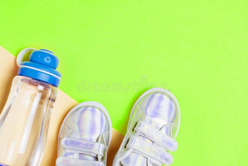 儿童运动鞋和瓶在绿色背景的水 免版税库存照片