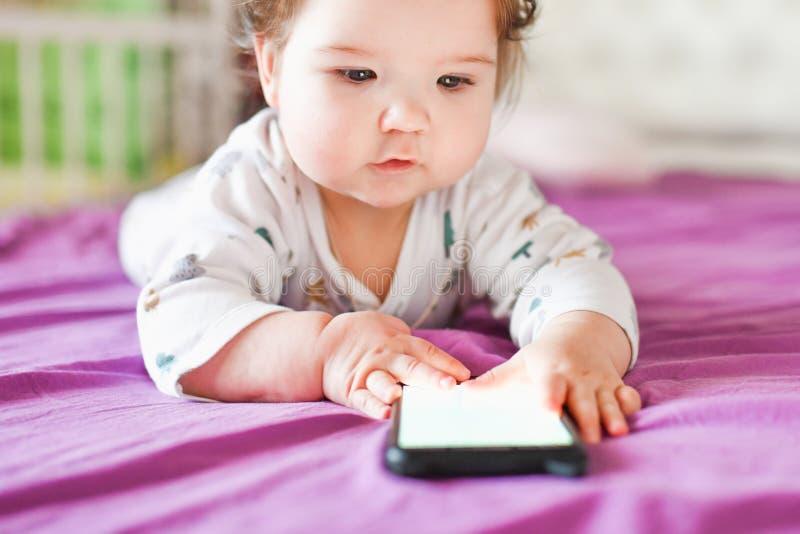 儿童通过手机学习 新生小婴儿用手机 库存照片