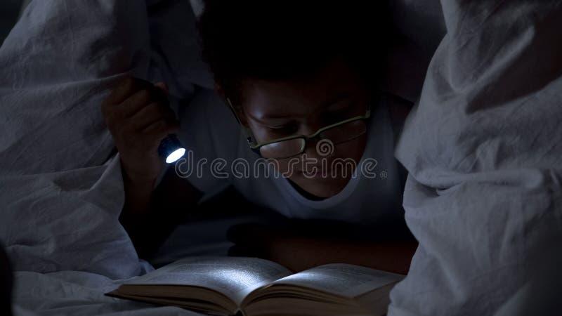 儿童阅读书在毯子下的晚上,与手电的照明设备  免版税库存照片