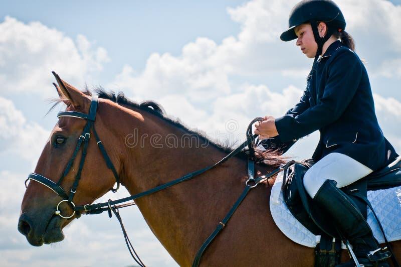 儿童骑马女孩跳车手显示体育运动 免版税库存图片