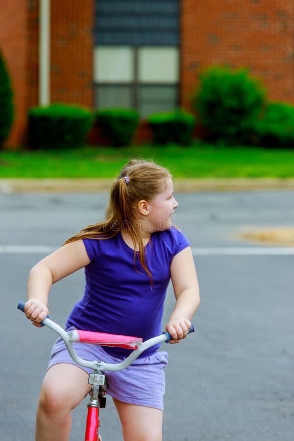 儿童骑马自行车 在自行车的孩子在晴朗的公园 享受在她的途中的小女孩自行车乘驾对学校在温暖的夏日 免版税图库摄影
