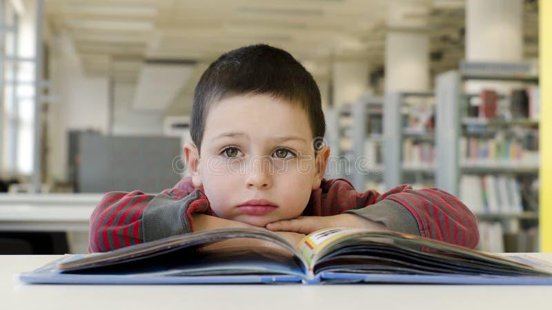 儿童读书和作白日梦。 免版税库存照片