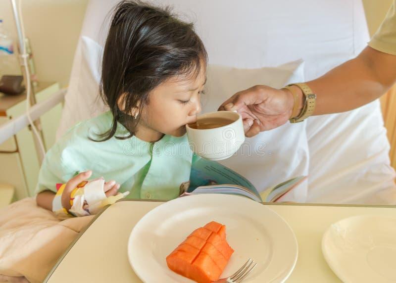 儿童医院患者吃并且喝帮助由父亲 免版税库存照片