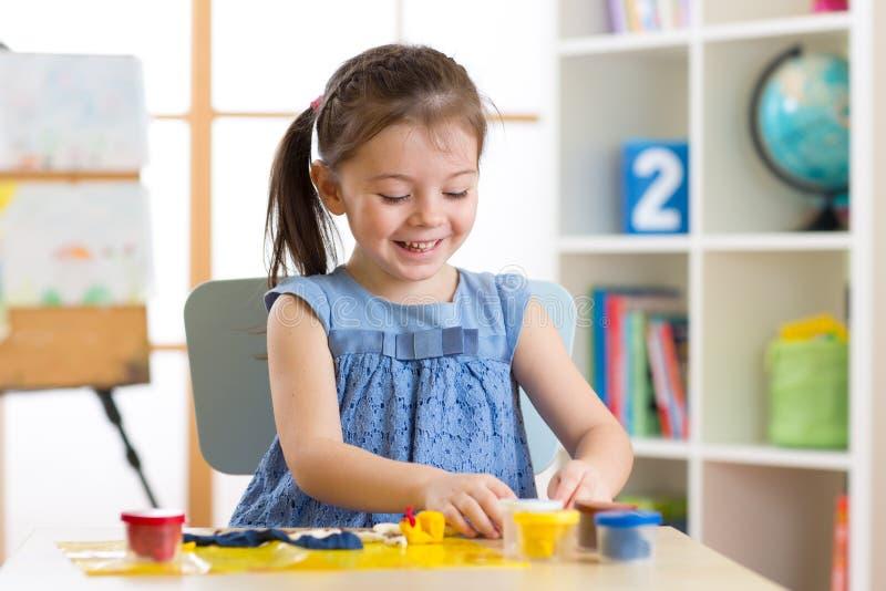 儿童` s创造性 孩子从黏土雕刻 逗人喜爱的小女孩从在桌上的彩色塑泥铸造 免版税库存照片