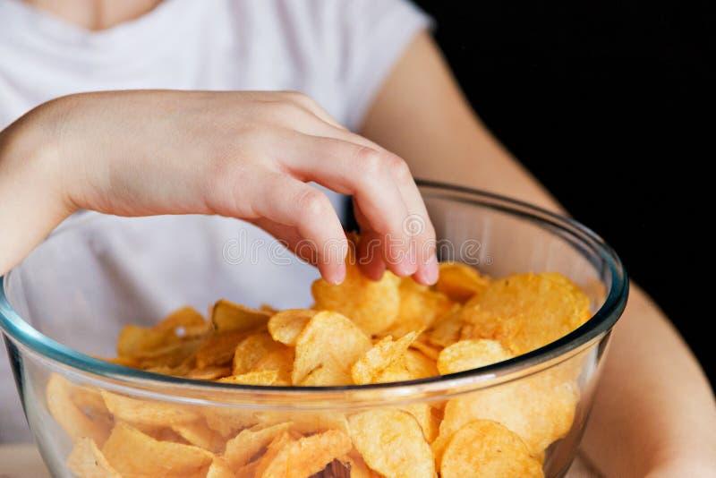 儿童` s手采取芯片在玻璃碗,有害的食物外面 免版税库存图片