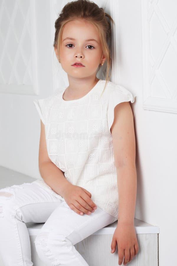 儿童` s时尚 whi的美丽的沉思严肃的白肤金发的女孩 免版税库存照片