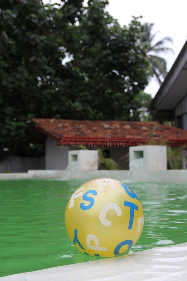 儿童` s漂浮在水池的黄色球 图库摄影