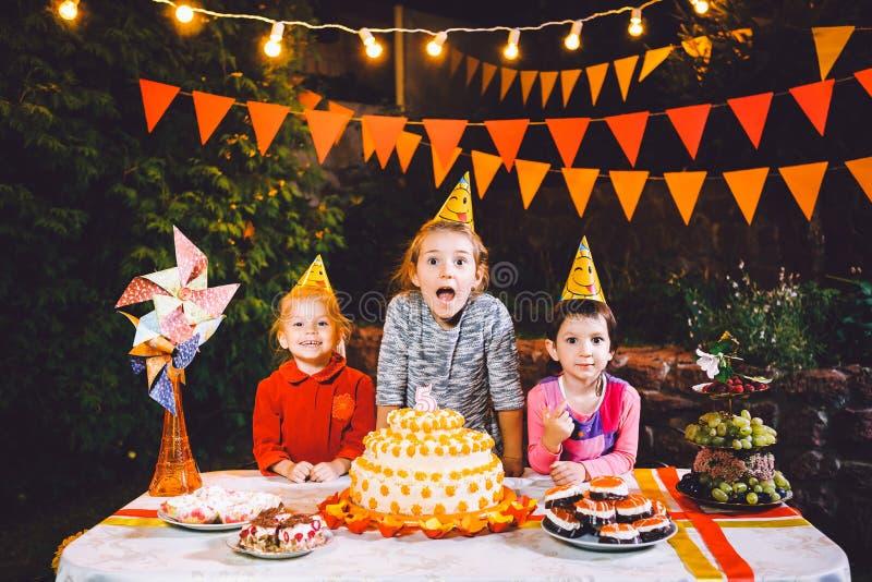 儿童` s生日聚会 在桌上吃蛋糕用他们的手和抹上他们的面孔的三个快乐的儿童女孩 乐趣a 库存图片