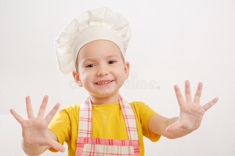 儿童` s细节递揉的面团 盖帽的快乐的厨师儿童男孩准备面卷饼 图库摄影