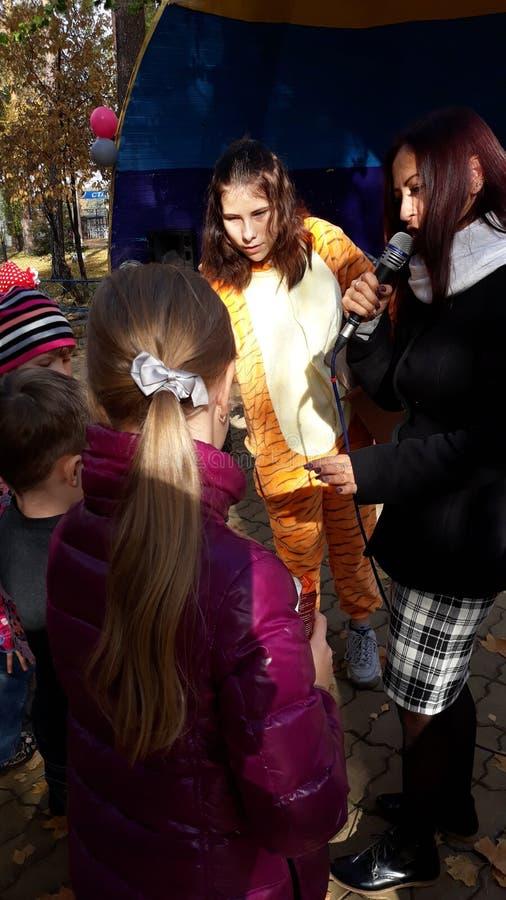 儿童` s艺人长颈鹿给礼物 有话筒的赠送者 图库摄影
