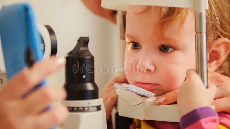 儿童` s视力测定-小女孩检查在眼睛眼科诊所的眼力-接近  图库摄影
