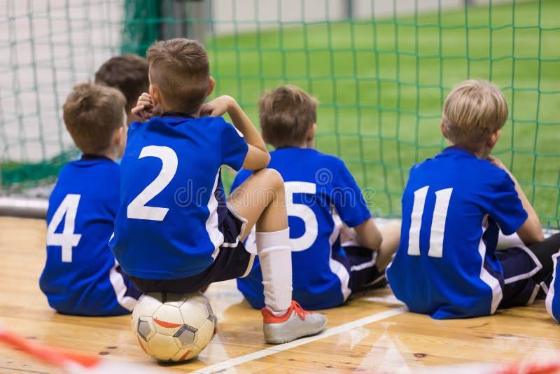 儿童futsal队 一起坐小组年轻室内足球的球员 库存图片