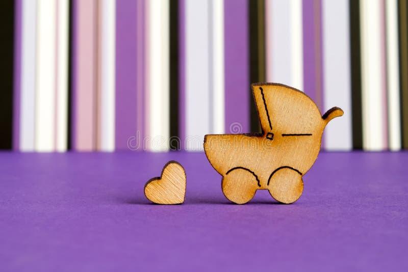 婴儿车和一点心脏木象在紫色镶边的 库存照片
